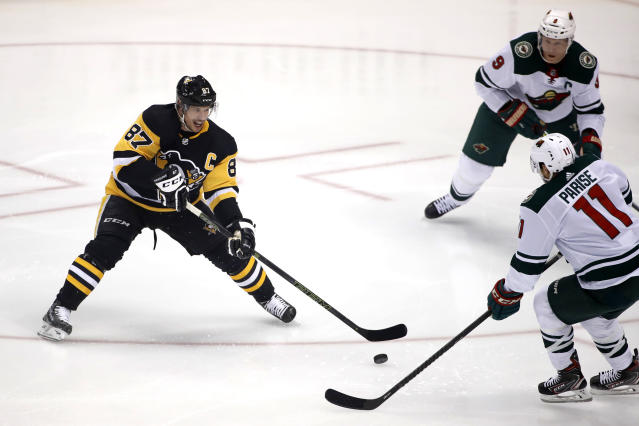 Pittsburgh Penguins' Sidney Crosby (87) gets off a pass with Minnesota Wild's Zach Parise (11) and Mikko Koivu (9) defending during the first period of an NHL hockey game in Pittsburgh, Tuesday, Jan. 14, 2020. Crosby hadn't played since undergoing abdominal surgery on Nov. 14. (AP Photo/Gene J. Puskar)