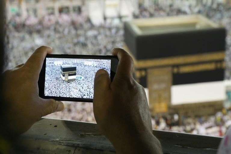 A man takes a picture of Muslim worshippers performing prayers around the Kaaba, Islam's holiest shrine, at the Grand Mosque in Saudi Arabia's holy city of Mecca on August 15, 2018