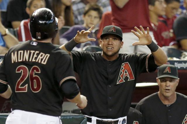 Arizona Diamondbacks' Miguel Montero (26) celebrates his run scored against the Chicago Cubs with teammate David Peralta, middle, and manager Kirk Gibson, right, during the fifth inning of a baseball game on Saturday, July 19, 2014, in Phoenix. Montero had a 3-run double when he batted in the fifth inning. (AP Photo/Ross D. Franklin)