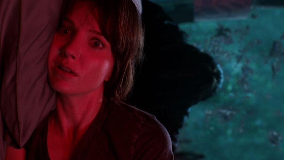 A woman in red lying down in Malignant's trailer