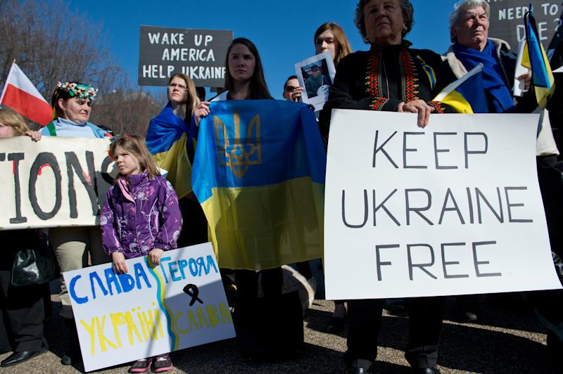 People hold signs and flags during a protest against ousted Ukrainian president Viktor Yanukovych in front of the White House in Washington on Feb. 23, 2014. (Photo: Nicholas Kamm/AFP/Getty Images)