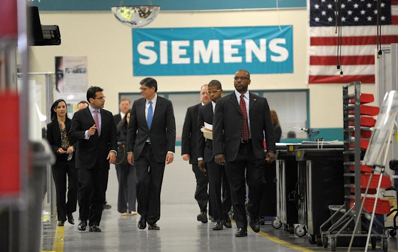 Treasury Secretary Jacob Lew, center, tours the Siemens manufacturing plant with Siemens Industry North America CEO Helmuth Ludwig, left, where electrical components for heavy machinery are assembled in Alpharetta, Ga., Thursday, March 14, 2013. The facility produces large traction drive trains for customers including AMTRAK, Caterpillar and the new Atlanta Streetcar initiative. (AP Photo/David Tulis)