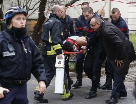 Firefighters carry a victim on a stretcher at the scene after a shooting at the Paris offices of Charlie Hebdo, January 7, 2015.   REUTERS/Jacky Naegelen