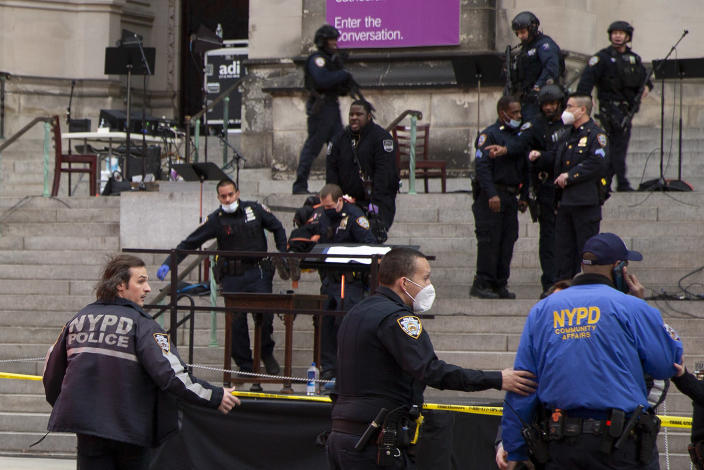 New York police officers carry a suspected gunman in a stretcher down the steps of Cathedral Church of St. John the Divine, Sunday, Dec. 13, 2020, in New York. A man was shot by police after shots rang out at the end of a Christmas choral concert on the steps of the Manhattan cathedral Sunday afternoon. It's unclear if the gunman was killed or if any others were injured. The shooting happened just before 4 p.m. at the church which is the mother church of the Episcopal Diocese of New York and seat of its bishop. (AP Photo/Ted Shaffrey)
