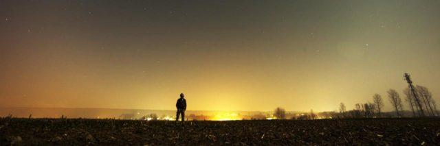 man outside far away with night sky and setting sun