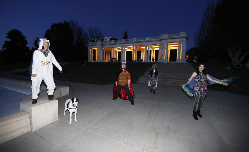 In this Wednesday, April 8, 2020, photograph, Irina Bocomolova and her dog, Darby, join Brice Maiurro, Shelsea Ochoa and Anna Beazer, from left, in a group howl in Cheesman Park in Denver. From California to New York, some Americans are taking a moment each night at 8 o'clock to howl as a way of thanking the health care workers and first responders who are fighting the coronavirus pandemic. (AP Photo/David Zalubowski)