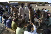 Soldiers serve breakfast to railway workers before they start the work to clear the track at the site of a train collision in the Ghotki district, southern Pakistan, Tuesday, June 8, 2021. The death toll from a deadly train accident in southern Pakistan jumped to dozens on Tuesday after rescuers pulled a dozen more bodies from crumpled cars of two trains that collided on a dilapidated railway track a day ago, an official said, as rescue work continued even 24 hours after the incident to find any survivors. (AP Photo/Fareed Khan)