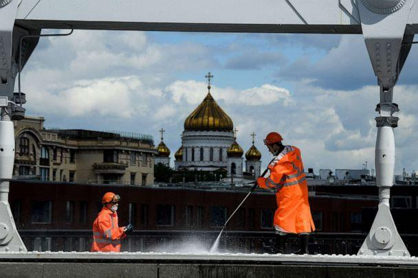 PHOTO: Municipal workers wearing face masks clean Krymsky Bridge across the Moskva river, with the Cathedral of Christ the Saviour seen in the background, in downtown Moscow, Russia, on May 20, 2020, amid the coronavirus pandemic. (Kirill Kudryavtsev/AFP via Getty Images)