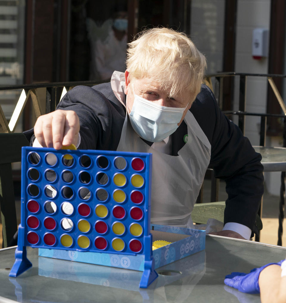 Britain's Prime Minister Boris Johnson plays Connect 4, during a visit to Westport Care Home in Stepney Green, east London, Tuesday, Sept. 7, 2021, ahead of unveiling his long-awaited plan to fix the broken social care system. (Paul Edwards/Pool Photo via AP)