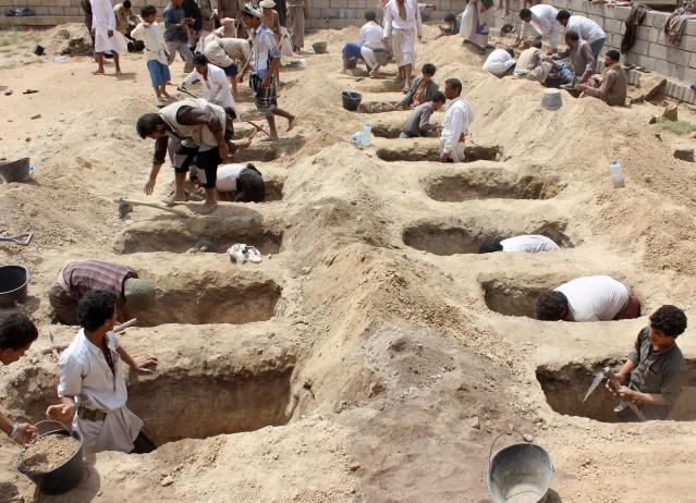 <p>Yemenis dig graves for children, who where killed when their bus was hit during a Saudi-led coalition air strike, that targeted the Dahyan market the previous day in the Huthi rebels' stronghold province of Saada on Aug. 10, 2018. (Photo: Stringer/AFP/Getty Images) </p>