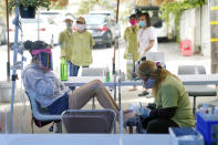 FILE - In this July 22, 2020, file photo, Tyson Salomon, left, gets a pedicure outside Pampered Hands nail salon in Los Angeles. Gov. Gavin Newsom announced a new, color-coded process Friday, Aug. 28, 2020, for reopening California businesses amid the coronovirus pandemic that is more gradual than the state's current rules to guard against loosening restrictions too soon. Counties will move through the new, four-tier system based on their number of cases and percentage of positive tests. It will rely on those two metrics to determine a tier: case rates and the percentage of positive tests. (AP Photo/Ashley Landis, File)