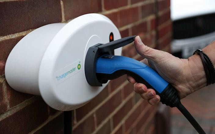 A person places an electric charging cable into BP Chargemaster electric vehicle charging point at a residential home - Andrew Matthews/PA