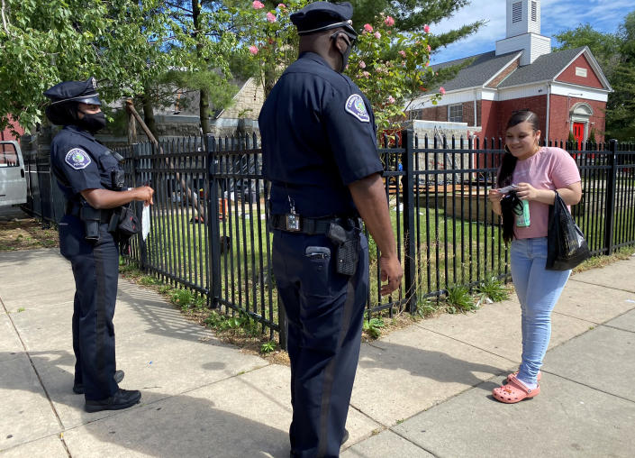 Image: Camden County Metro Police Lt. Zack James and Officer Mayah Bailey speak to a resident. (Kenzi Abou-Sabe / NBC News)