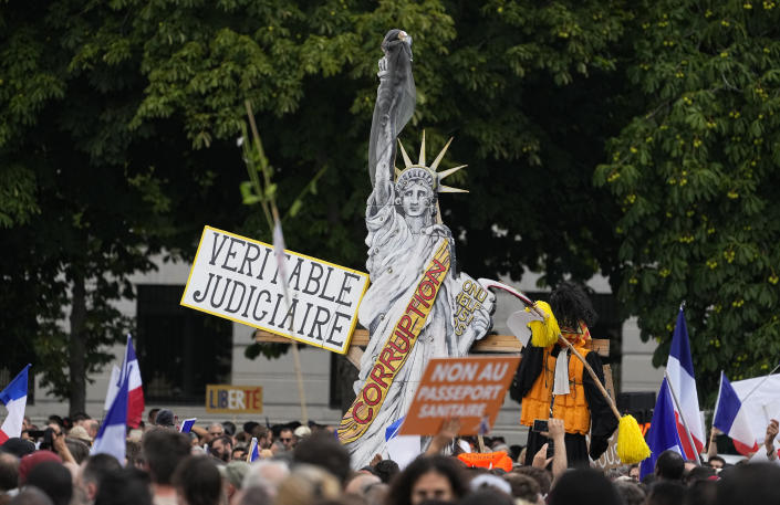 """Protestors wave French flags and hold signs in front of a cardboard cutout of the Statue of Liberty during a demonstration in Paris, France, Saturday, July 31, 2021. Demonstrators gathered in several cities in France on Saturday to protest against the COVID-19 pass, which grants vaccinated individuals greater ease of access to venues. Sign reads in French """"True Judiciary"""". (AP Photo/Michel Euler)"""