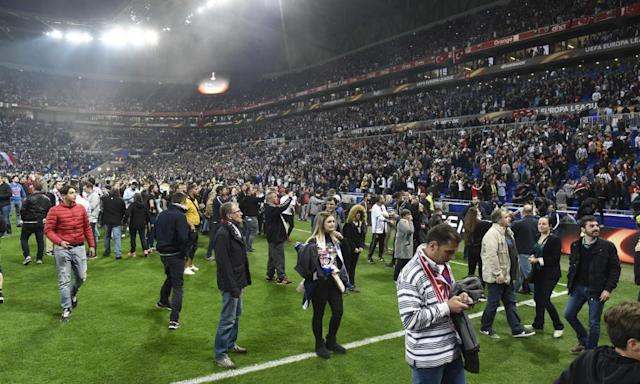 """<span class=""""element-image__caption"""">Supporters take refuge on the Parc OL pitch as other fans fight in the stands before the Europa League tie between Lyon and Besiktas.</span> <span class=""""element-image__credit"""">Photograph: Philippe Desmazes/AFP/Getty Images</span>"""