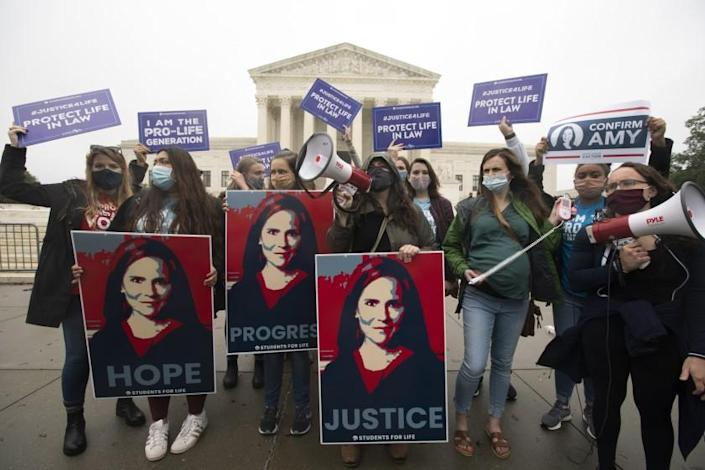 Supporters of President Donald Trump's Supreme Court nominee Amy Coney Barrett, rally at the Supreme Court in Washington, Monday, Oct. 12, 2020. Barrett's confirmation hearing begins Monday before the Republican-led Senate Judiciary Committee. (AP Photo/Jose Luis Magana)