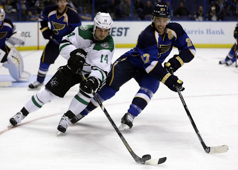 Dallas Stars' Jamie Benn, left, reaches for the puck as St. Louis Blues' Alex Pietrangelo defends during the third period of a preseason NHL hockey game Saturday, Sept. 21, 2013, in St. Louis. The Blues won 3-2 in overtime. (AP Photo/Jeff Roberson)