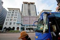 Tourists get off a bus outside The Peninsula hotel in Hong Kong