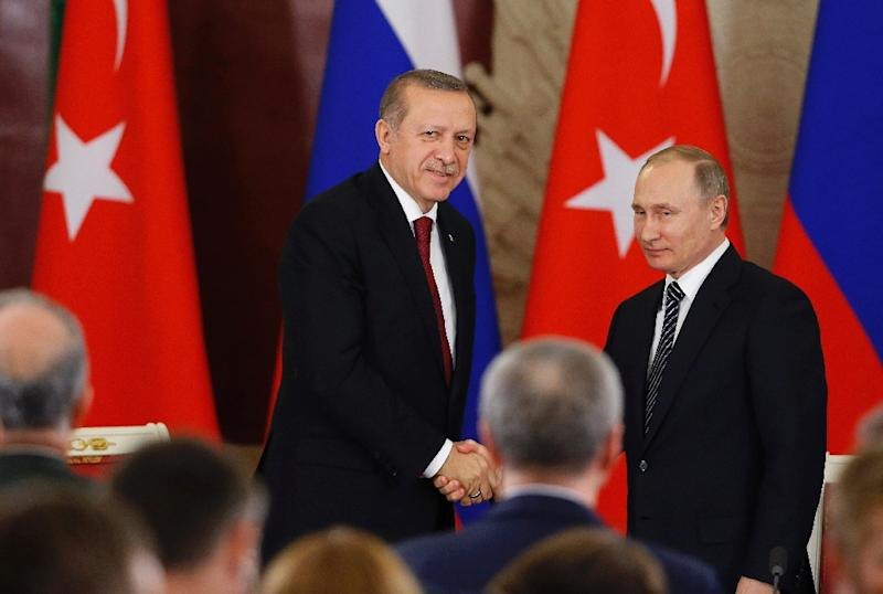 Russian President Vladimir Putin (R) and Turkey's President Recep Tayyip Erdogan shake hands after a joint news conference following their talks at the Kremlin in Moscow on March 10, 2017