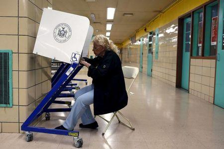 A woman fills out a ballot at a polling center during the New York primary elections in the East Harlem neighborhood of New York City, U.S.