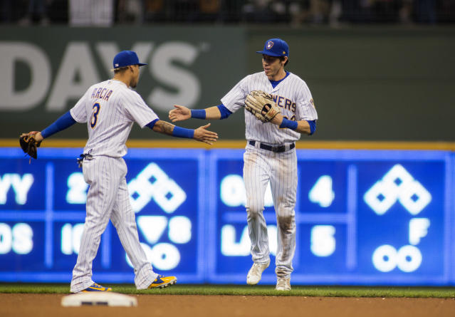Milwaukee Brewers center fielder Christian Yelich, right, is congratulated by team mate Orlando Arcia, left, as he is pulled from the game against the Detroit Tigers during the eighth inning of an baseball game Sunday, Sept. 30, 2018, in Milwaukee. (AP Photo/Darren Hauck)