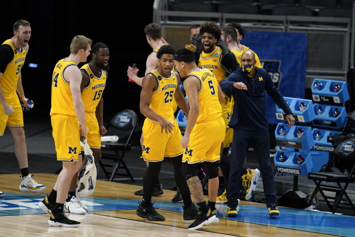 Michigan players celebrate at the end of a Sweet 16 game against Florida State in the NCAA men's college basketball tournament at Bankers Life Fieldhouse, Sunday, March 28, 2021, in Indianapolis. Michigan won 76-58. (AP Photo/Jeff Roberson)