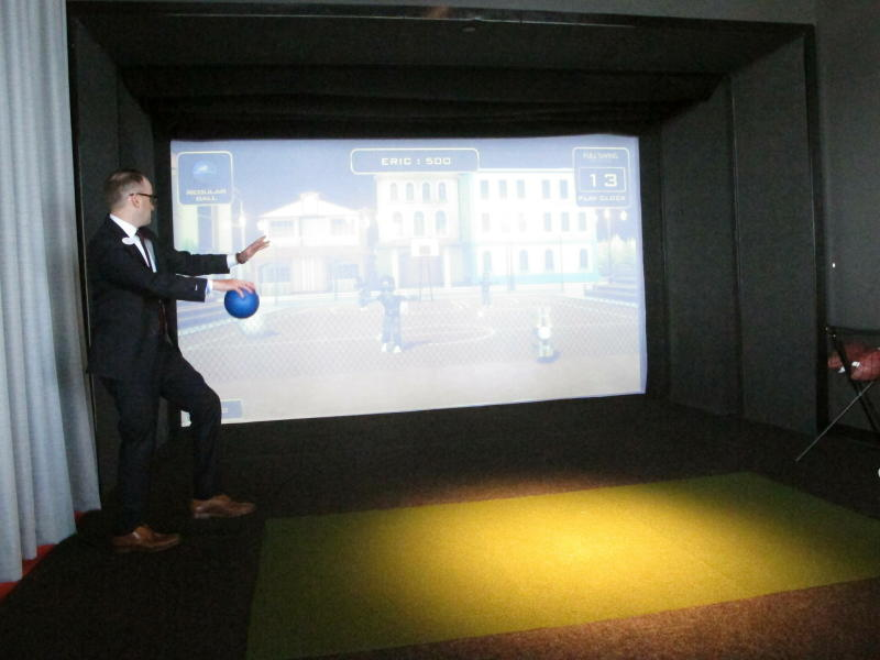 This April 30, 2019 photo shows Mike Donovan, chief marketing officer for the Ocean Casino Resort, playing a game of virtual dodge ball at a sports simulator at the Atlantic City N.J. casino. The casino formerly known as Revel will turn a profit in May after months of steep losses. (AP Photo/Wayne Parry)