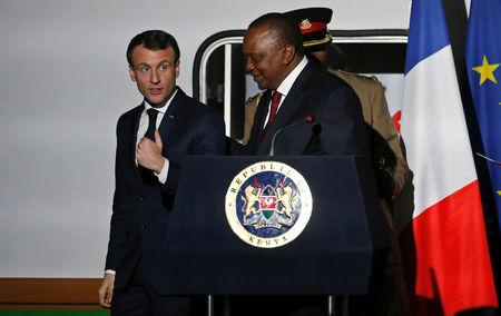 FILE PHOTO: French President Emmanuel Macron talks to Kenya's President Uhuru Kenyatta as they leave a news conference after touring the Nairobi Central Railway in Nairobi, Kenya March 13, 2019. REUTERS/Thomas Mukoya/File Photo