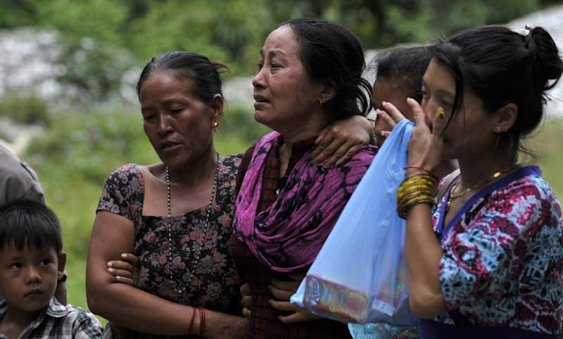 Nepalese villagers grieve following the deaths of family members in a landslide at Lamo Sanghu on the Sukoshi river, some 80 kms northeast of Kathmandu, on August 6, 2014 (AFP Photo/Prakash Mathema)