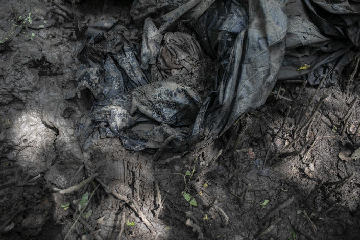 Clothes and black plastic bags lay on the ground at a clandestine grave site in Puquita, a tropical mangrove island near Alvarado in the Gulf coast state of Veracruz, Mexico, Thursday, Feb. 18, 2021. Investigators from the National Search Commission found three pits with human remains and plastic bags inside. The number of bodies there has not yet been determined. (AP Photo/Felix Marquez)