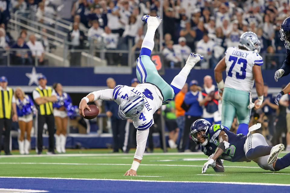 Cowboys quarterback Dak Prescott dives for the end zone during the NFC wild-card game against the Seahawks. Prescott ran for a score, threw for another, and completed 22 of 33 passes for 226 yards and an interception in Saturday's win. (Getty Images)