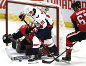 Ottawa Senators goaltender Mike McKenna (33) uses his stick to control the puck in the crease as defenseman Ben Harpur (67) tries to force back the stick of Washington Capitals center Nicklas Backstrom (19) during the third period of an NHL hockey game, Saturday, Dec. 22, 2018, in Ottawa, Ontario. (Justin Tang/The Canadian Press via AP)