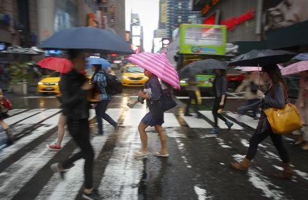 People cross the road in the rain at Times Square in New York