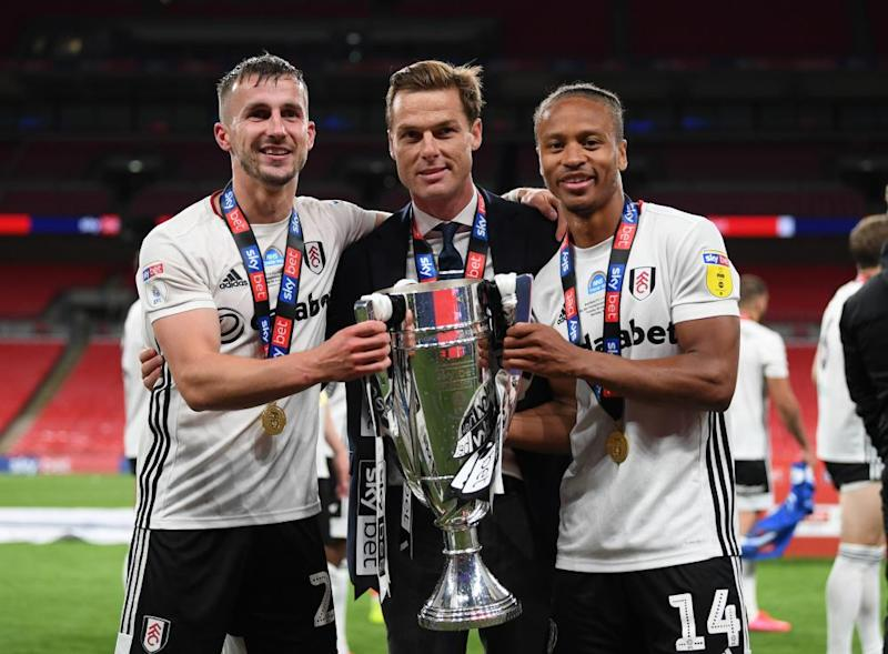 Joe Bryan (left) and Bobby Decordova-Reid hold the trophy with the Fulham manager, Scott Parker.