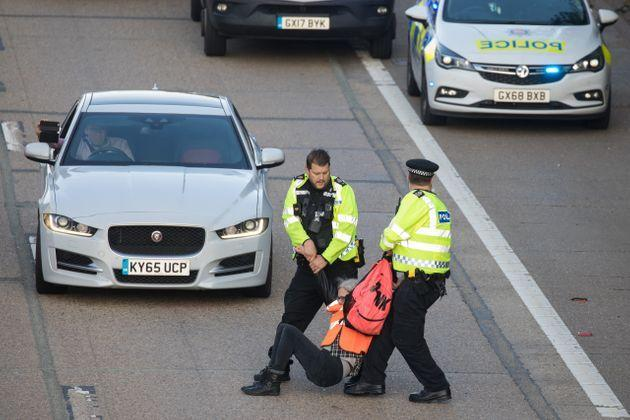 <strong>Surrey Police officers haul an Insulate Britain climate activist from the carriageway of the M25.</strong> (Photo: Mark Kerrison via Getty Images)