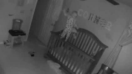 The baby balances on the side of his crib, in a scene that looks like a clip from Paranormal Activity. Photo: YouTube