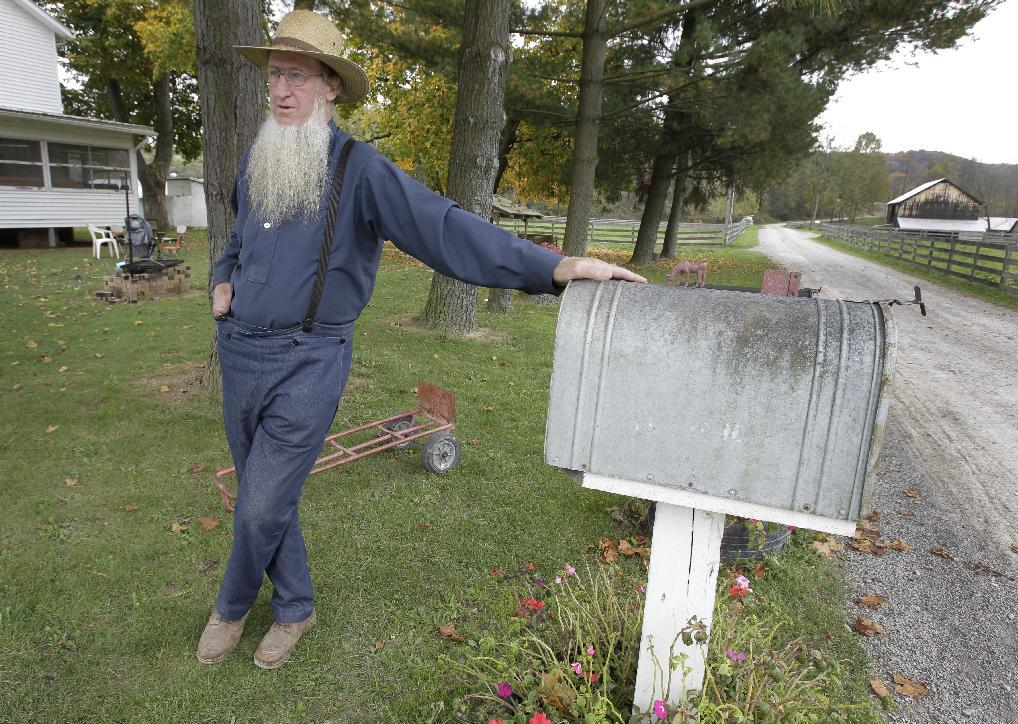 FILE- In this Oct. 10, 2011 file photo, Sam Mullet, father of two of the three men arrested for allegedly going into the home of other Amish and cutting their hair and beards, is seen outside his home in Bergholz, Ohio. Leaders within the Amish community faced a soul-searching question after hair-cutting attacks against several followers of their faith. Should they cooperate with authorities or follow the deeply held belief of forgiveness toward one another? In the end, they decided the only way to stop the attacks was to seek help from the outside. ( AP Photo/Amy Sancetta)
