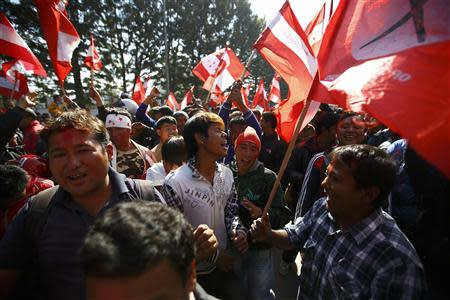Supporters of the Nepali Congress Party cheer for their party as the Constituent Assembly Election scores are displayed on a screen in Kathmandu