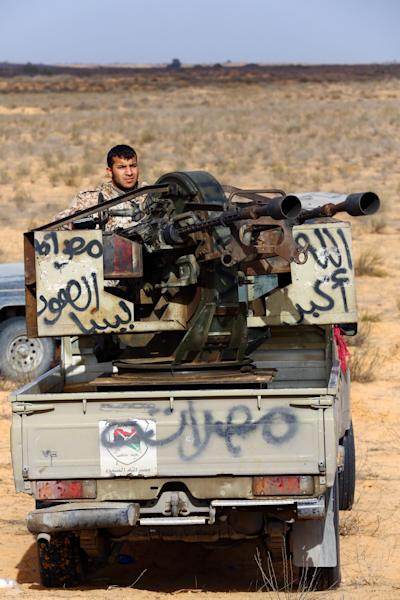 A fighter from the Fajr Libya (Libya Dawn) militia sits on a pick up truck mounted with a machine gun some 170 kilometres west of the capital Tripoli on January 5, 2015 (AFP Photo/Mahmud Turkia)