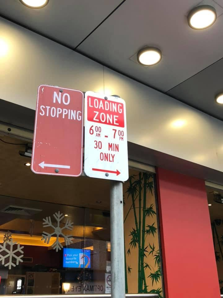 A sign that stipulates an area is a loading zone from 6am to 7am and 30 minute parking only applies.