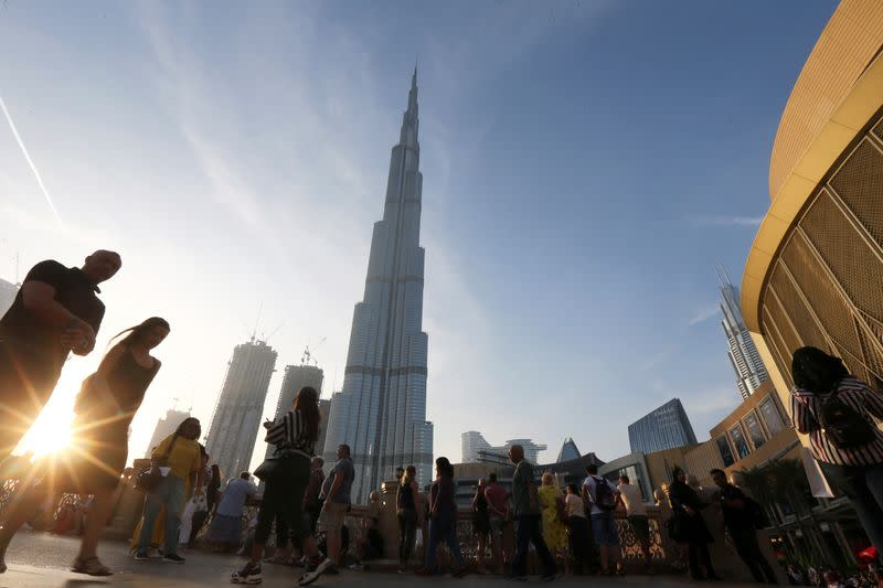 People are seen in front of Burj Khalifa, the world tallest building, in Dubai