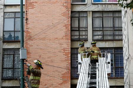 Firefighters stand outside a building damaged by an earthquake that struck off the southern coast of Mexico late on Thursday, in Mexico City