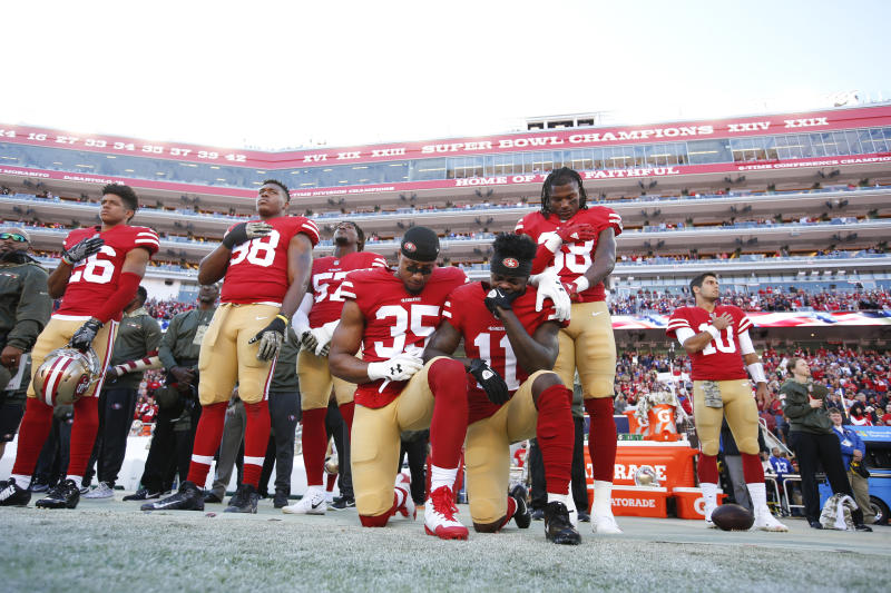 Reid, left, and teammate Marquise Goodwin, right, kneel during the anthem on Nov. 12, 2017, in Santa Clara, California. (Michael Zagaris via Getty Images)