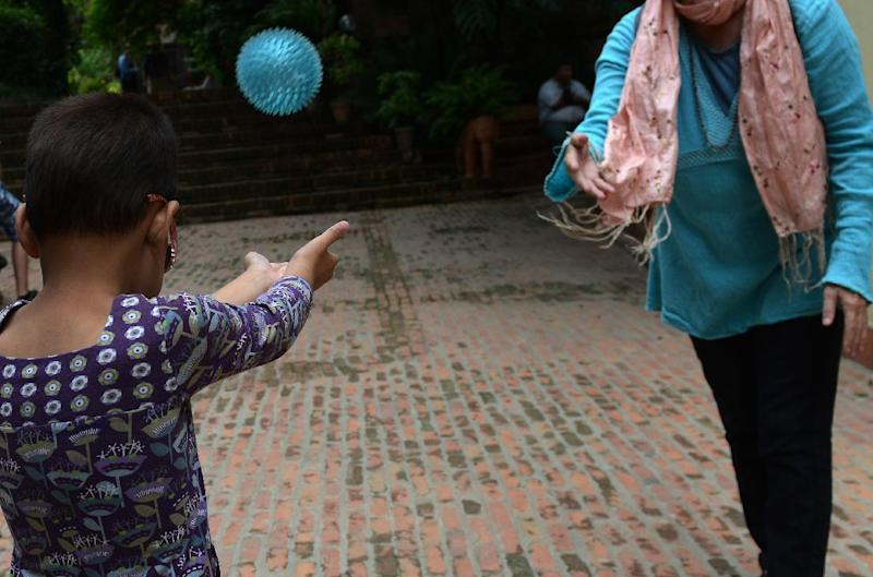 A seven-year-old blind girl who goes under the pseudonym Anna plays with her adoptive mother outside a restaurant in Kathmandu on July 23, 2014 (AFP Photo/Prakash Mathema)