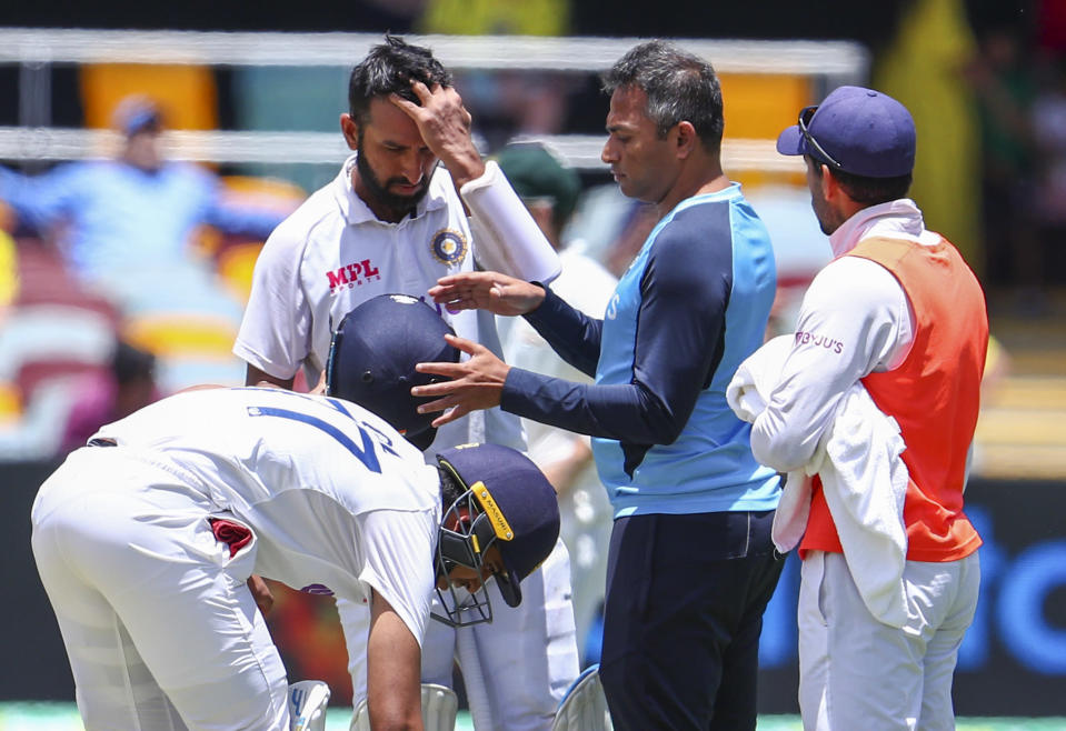 India's Cheteshwar Pujara is checked by a trainer after he was hit on the helmet while batting during play on the final day of the fourth cricket test between India and Australia at the Gabba, Brisbane, Australia, Tuesday, Jan. 19, 2021. (AP Photo/Tertius Pickard)