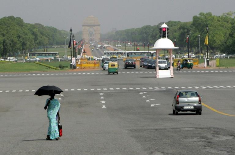 A woman in New Delhi carries an umbrella to protect herself from the blazing sun, one way of avoiding a darker complexion
