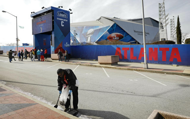 John Chavis sweeps the street in front of Mercedes-Benz Stadium ahead of Sunday's NFL Super Bowl 53 football game between the Los Angeles Rams and New England Patriots in Atlanta, Friday, Feb. 1, 2019. (AP Photo/David Goldman)