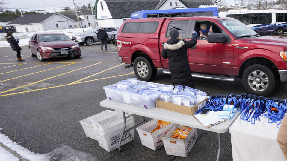 Staff members distribute mobile voting devices to state representatives as they arrive for an outdoor meeting of the New Hampshire House of Representatives in a parking lot, due to the COVID-19 virus outbreak, at the University of New Hampshire Wednesday, Jan. 6, 2021, in Durham, N.H. (AP Photo/Charles Krupa)