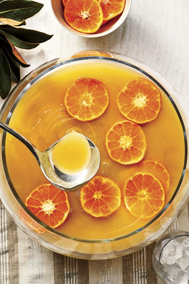"""<p><b>Recipe: </b><a href=""""https://www.southernliving.com/recipes/spicy-bourbon-citrus-punch""""><strong>Spicy Bourbon-Citrus Punch</strong></a></p> <p>Top this bright orange punch with fake spiders to complete the Halloween look.</p>"""