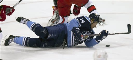 Florida Panthers' player Tomas Fleischmann covers the puck after being knocked to the ice by a Carolina Hurricanes player during the first period of an NHL hockey game in Sunrise, Fla., Sunday, March 11, 2012. (AP Photo/J Pat Carter)